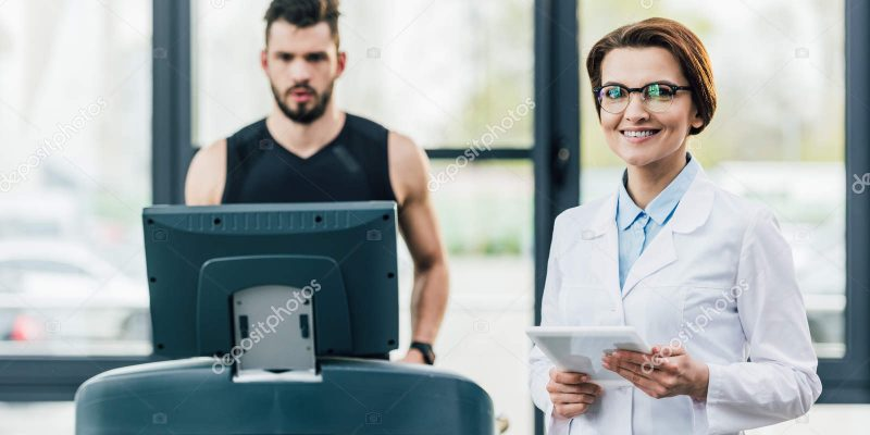 depositphotos_273810966-stock-photo-sportsman-running-treadmill-smiling-doctor